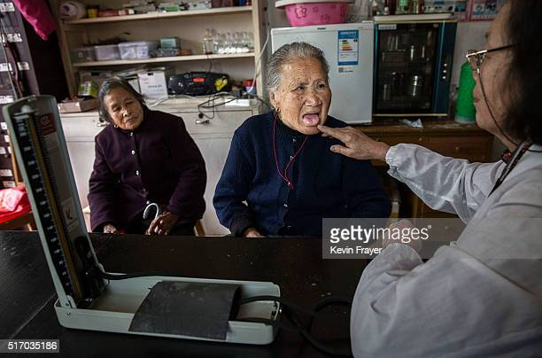 Chinese Doctor Li Laifeng who has volunteered for the last 20 years checks an elderly Chinese resident in the small clinic at the Ji Xiang Temple and...