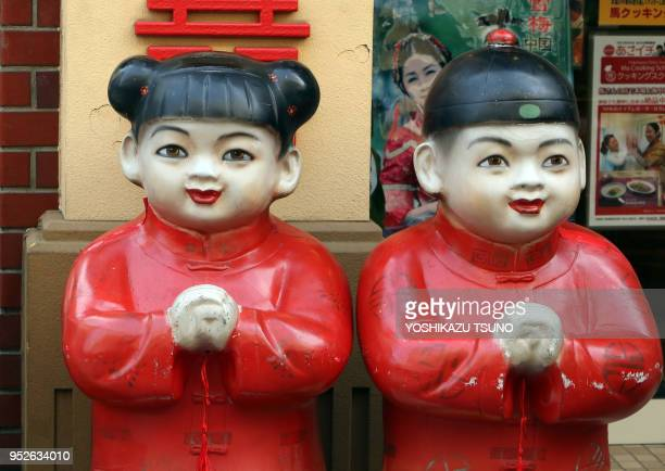 Chinese dolls stand in front of a Chinese restaurant at Yokohama Chinatown as Chinese Lunar New Year started in Yokohama suburban Tokyo on January 29...