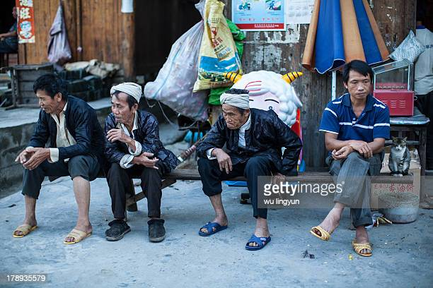 Chinese Dong men sitting in a row by the street after dinner.