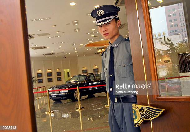 Chinese doorman welcomes customers to the Bentley car showroom June 20 2003 in Beijing China With than 10 million cars already in private ownership...