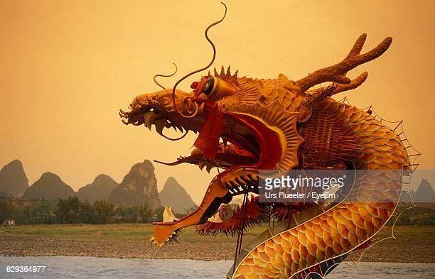 chinese dragon by lake during sunset - chinese dragon stock photos and pictures