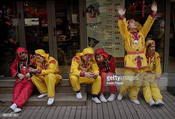 Chinese dragon dancer stretches as other performers look at their smart phones during a break while shooting a film in the Sanlitun area on April 3...