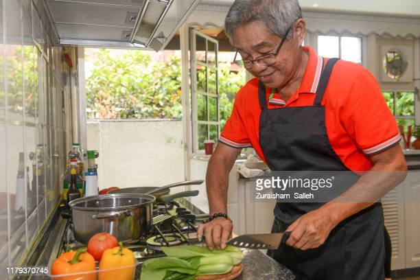 chinese elderly man cooking at home during chinese new year - 70 year old man stock pictures, royalty-free photos & images