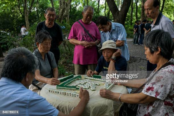 Chinese elderly people play Mahjong in a public park in Shanghai on September 14 2017 / AFP PHOTO / CHANDAN KHANNA