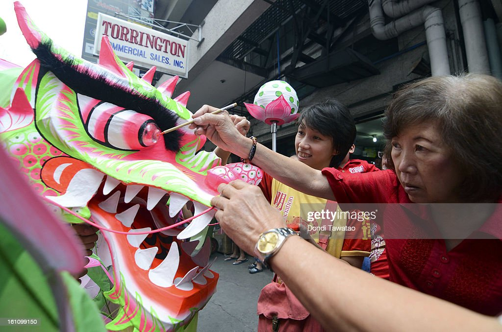 Chinese elders apply eyelids to a lotus dragon during the celebration of the Chinese New Year in the district of Binondo on February 9, 2013 in Manila, Philippines. Only after being fitted with eyelids can a dragon 'come to life', according to traditional Chinese dragon makers. The Chinese New Year begins tomorrow and this year is the year of the snake, known by locals as 'Spring Festival' or 'Lunar New Year' it is celebrated annually by Chinese Filipinos who make up roughly 20 percent of the local population.