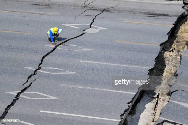 Chinese employee investigates the scene of accident after a road collapse in Foshan in China's southern Guangdong province on February 8 2018 Eight...