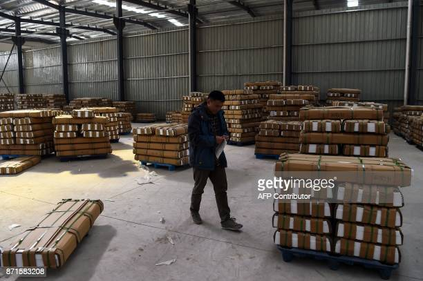 A Chinese employee of a company works inside a factory in Suining County at Jiangsu province on November 8 2017 US president Donald Trump landed in...