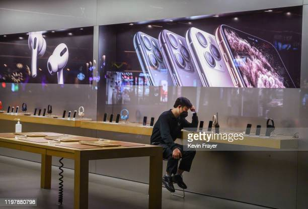 Chinese employee wears a protective mask as he sits in the showroom of an Apple Store after it closed for the day on February 1, 2020 in a shopping...
