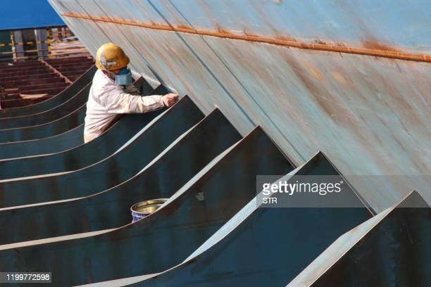 Chinese employee works at a shipyard in Nantong in China's eastern Jiangsu province on February 10, 2020. - Millions of people in China were...