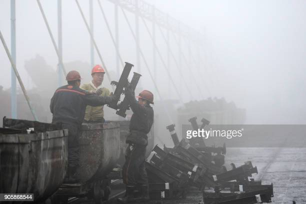 Chinese employees work during heavy fog in Huaibei in China's eastern Anhui province on January 17, 2018. / AFP PHOTO / - / China OUT