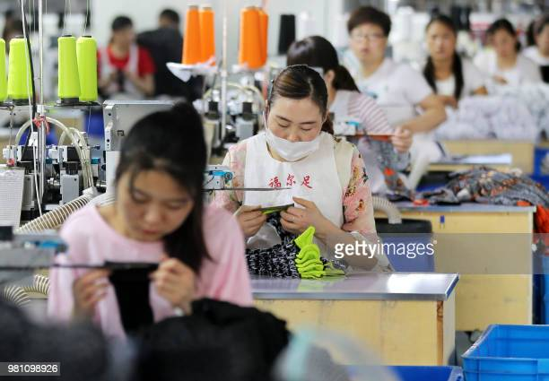 Chinese employees work on socks that will be exported at a factory in Huaibei in China's eastern Anhui province on June 22 2018 Beijing on June 19...