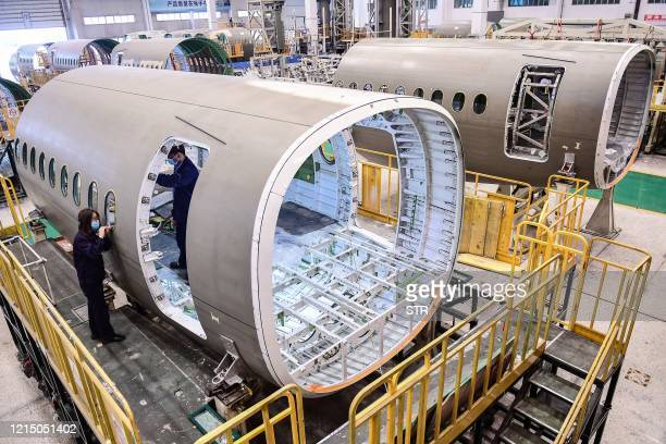 Chinese employees work on the fuselage of Airbus A220 aircraft at a factory in Shenyang in China's northeastern Liaoning province on May 25, 2020. /...