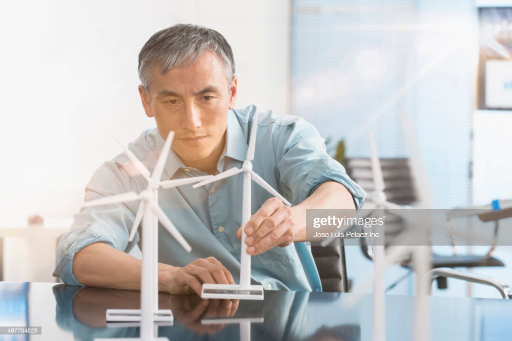 Chinese engineer examining model wind turbines in office : Stock Photo