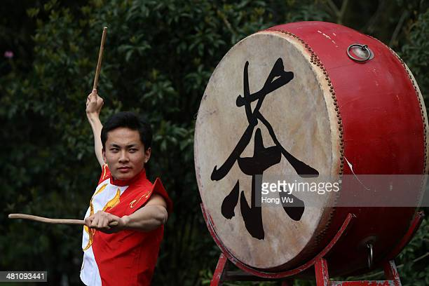 Chinese entertainer performs beside a drum with a Chinese character means 'Tea' on it during a ceremony for Longjing tea picking festival on March 28...
