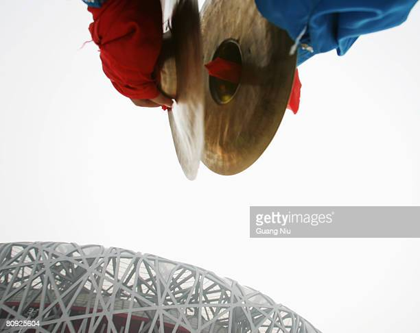 Chinese entertainer performs in front of the National Stadium, also known as the 'Bird's Nest' during a long-distance race on April 30, 2008 in...