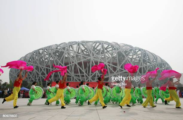 Chinese entertainers perform in front of the National Stadium, also known as the 'Bird's Nest' during a long-distance race on April 30, 2008 in...