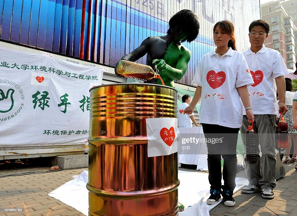 Chinese environmental volunteers collect used oil from restaurants to recycle it into soap, to raise attention to recycling and environment pollution, as they mark the World Environmental Day on June 6, 2010.Beijing has pledged to reduce its carbon intensity -- the measure of greenhouse-gas emissions per unit of gross domestic product -- by 40 to 45 percent by 2020 based on 2005 levels. CHINA