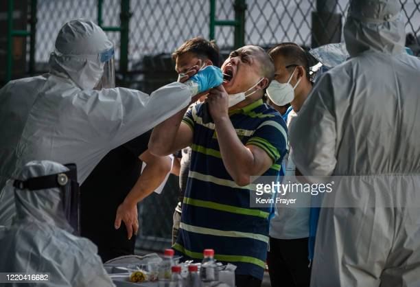 Chinese epidemic control worker wears a protective suit and mask while performing a nucleic acid test for COVID19 on a man who has had contact with...