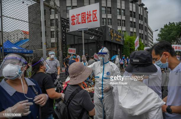 Chinese epidemic control worker wears a protective suit and mask as he and volunteers direct and register people at a site where authorities were...