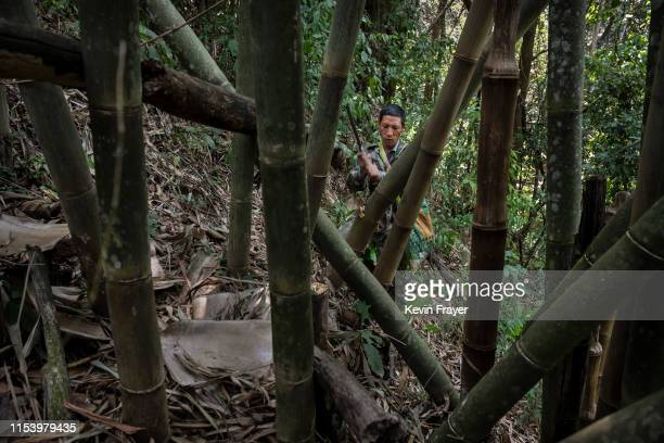 Chinese ethnic Lisu honey hunter Ma Yongde chops bamboo to make a container after gathering wild cliff honey from hives in a gorge on May 10 2019...