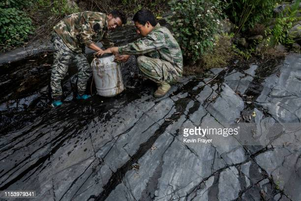 Chinese ethnic Lisu honey hunter Ma Yongde right and helper Dongwu washthe outside of a container of fresh honey while gathering wild cliff honey...