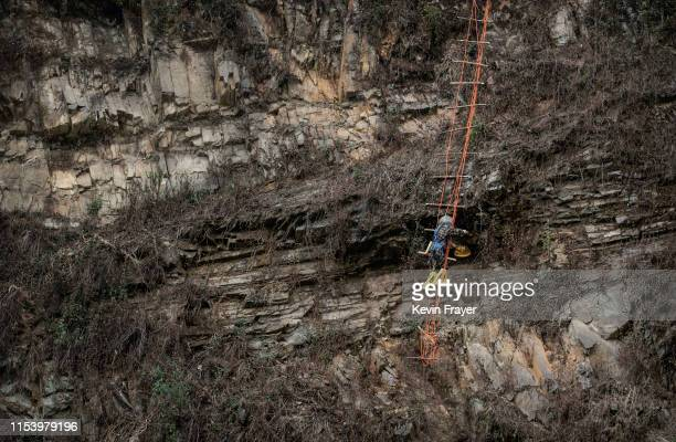 Chinese ethnic Lisu honey hunters Dong Haifa hangs on a makeshift ladder while gathering wild cliff honey from hives in a gorge on May 30 2019 near...