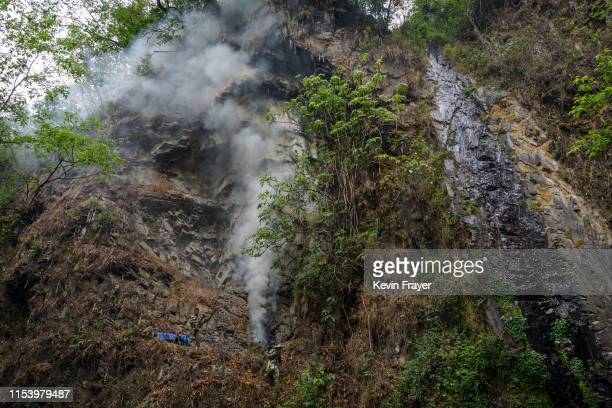 Chinese ethnic Lisu honey hunters light a fire to make smoke before gathering wild cliff honey from hives in a gorge on May 30 2019 near Mangshi in...
