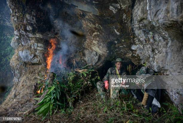 Chinese ethnic Lisu honey hunters Mi Qiaoyun right and Ma Yongde sit still next to a fire they set to deter bees before gathering wild cliff honey...