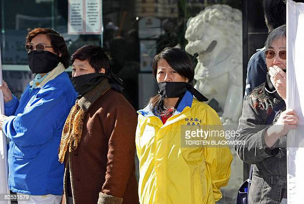 Chinese expatriates condemning media censorship wear gags over their mouths during a protest in Sydney on August 24 2008 Australia's Chinese...