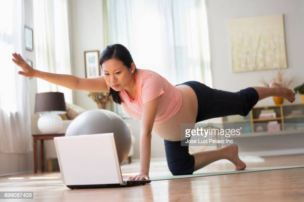 chinese expectant mother watching laptop performing yoga - mood stream stock pictures, royalty-free photos & images