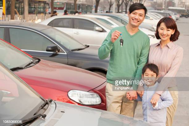 chinese family holding keys to new car - buying a car stock pictures, royalty-free photos & images
