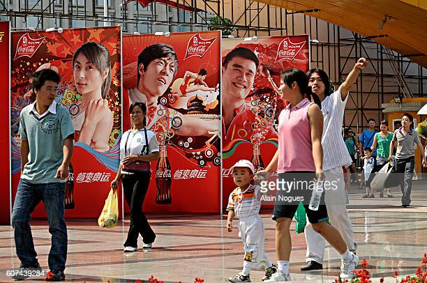 Chinese family in front of Coca Cola bilboards in Chaoyang Park featuring female diver Guo Jinjin basketball player Yao Ming and hurdler Liu Xiang...