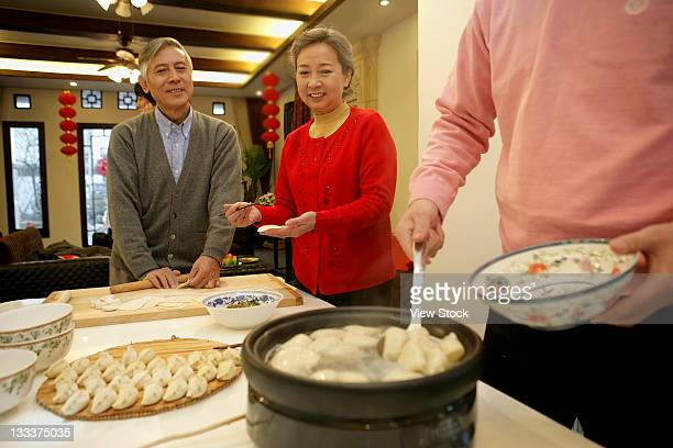 chinese family making chinese dumpling on new years eve - 25 29 years stock pictures, royalty-free photos & images