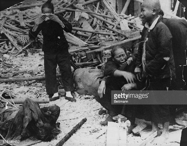 A Chinese family mourns the loss of family members as they sit with what remains of their home in Nanchang following an air raid by Japan