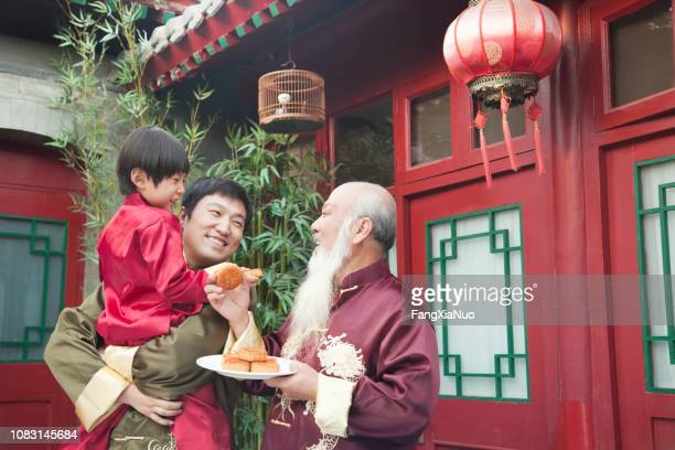 chinese family sharing plate of food outdoors - moon cake stock pictures, royalty-free photos & images