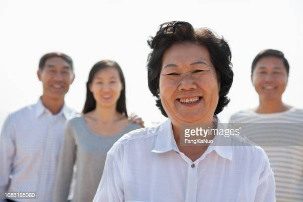 chinese family smiling outdoors - chinese mothers day stock pictures, royalty-free photos & images