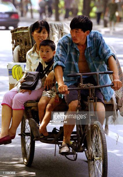 Chinese family travels on a tricycle July 24 2002 in Beijing China US government officials announced July 22 2002 that they will withhold $34 million...