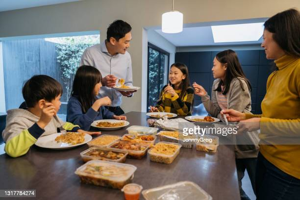 chinese family with four children eating takeout for dinner - chinese ethnicity stock pictures, royalty-free photos & images
