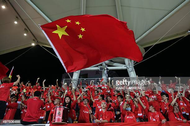 A Chinese fan waves the national flag during a world cup qualifier at Mong Kok stadium in Hong Kong on November 17 2015 Hong Kong fans booed the...