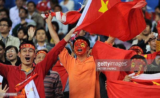 Chinese fans cheer for their athletes during day two action in the athletics competition at the 16th Asian Games in Guangzhou on November 22, 2010....