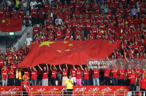 Chinese fans hold their national flag as they listen to their national anthem prior to the start of the FIFA World Cup 2018 qualification football...