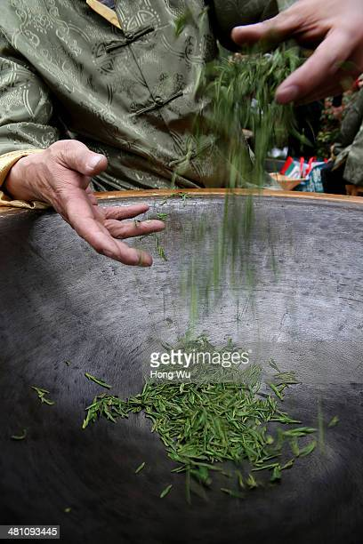 Chinese farmer fries fresh Longjing tea leaves using traditional technics by hands during a ceremony for Longjing tea picking festival on March 28...