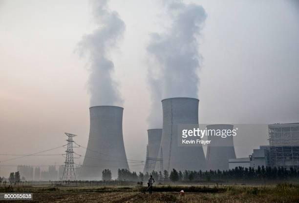 Chinese farmer works his field next to a state owned coal fired power plant near the site of a large floating solar farm project under construction...