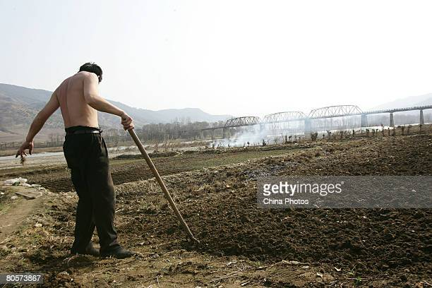 Chinese farmer works in a field on the river beach of Yalu River on April 8, 2008 in Linjiang of Jilin Province, China. Linjiang, Linjiang is...