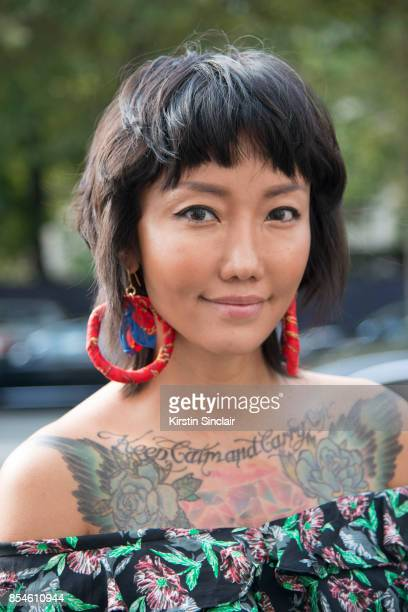 Chinese fashion blogger Carrie Lee wears a Dior top and earrings she made herself day 1 of Paris Womens Fashion Week Spring/Summer 2018 on September...