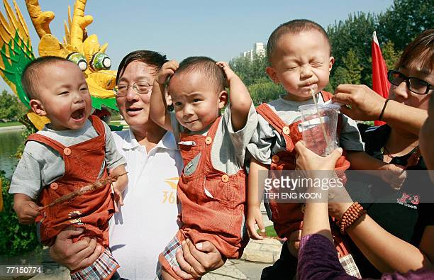 Chinese father and mother hold their triplet boys during the Beijing Twins Cultural Carnival at a park in Beijing 02 October 2007 Chinese officials...