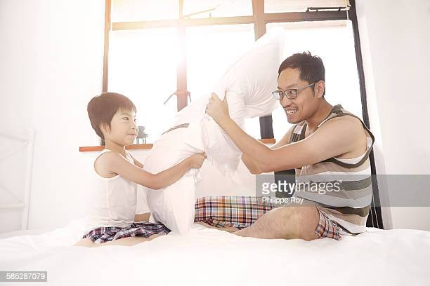 Chinese father and son having a pillow fight