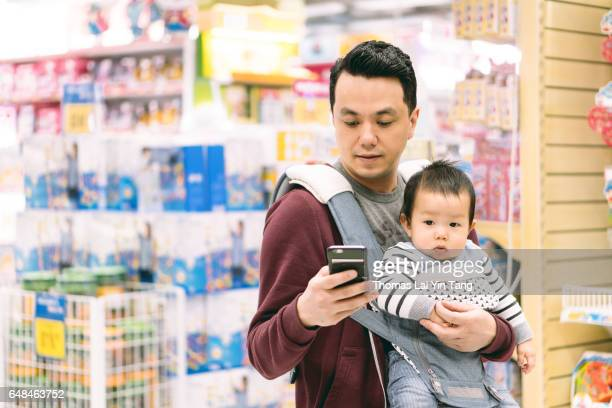 Chinese father checking mobile cell phone in supermarket while carrying 9 months old baby boy joyfully