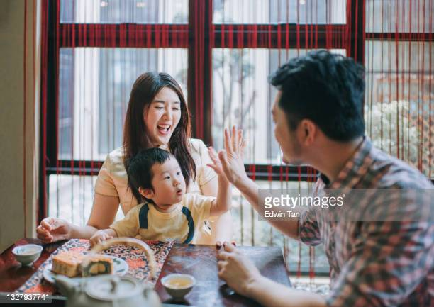 chinese father high five with son during enjoying traditional mid-autumn mooncake and chinese tea at home during afternoon tea gathering - moon cake stock pictures, royalty-free photos & images