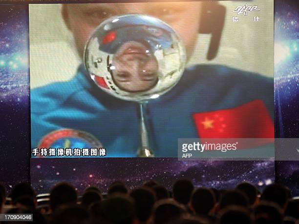 Chinese female astrounaut Wang Yaping is reflected in a drop of water floating in Tiangong1 space module as she delivers a lesson to students that...